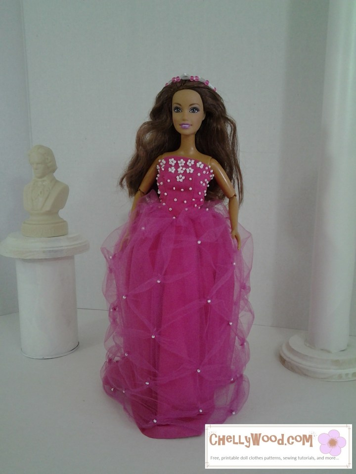 The image shows a Mattel Teresa doll in a pretty Quinceañera dresses with tiny white beaded flowers on the front of the pink bodice and a pink long skirt that's overcast by a gorgeous semi-gathered tulle layer on top.