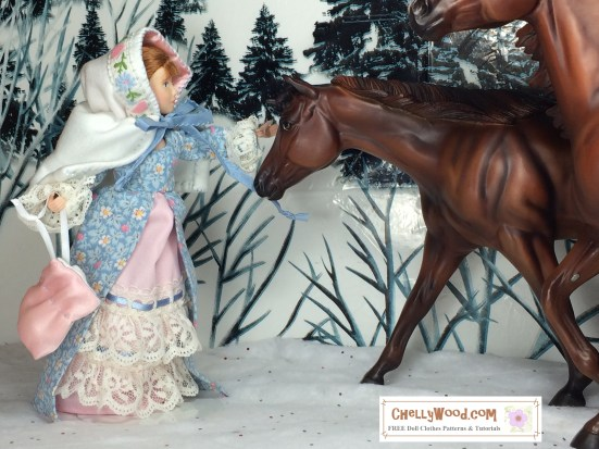 Image shows doll made by the Breyer company dressed in a pioneer dress made with lace and holding a satin drawstring purse. The doll, who also wears a short hooded cape, stretches out her hand to touch one of two horses walking through a snowy forest. Image is watermarked: ChellyWood.com: free printable sewing patterns and tutorials for dolls of many shapes and sizes.