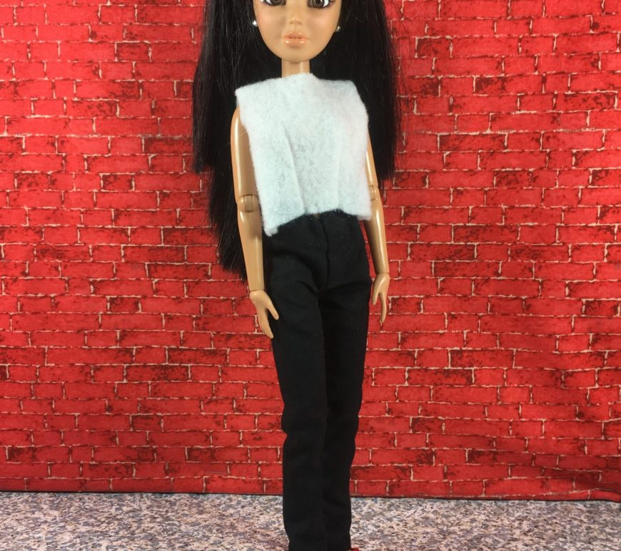 A Spin Master Liv doll wears a pair of black elastic-waist pants and a simple white felt shirt. She stands in front of a red brick wall on a concrete floor. Her hair is long and black with bangs (fringe). She wears a pair of red and black handmade slip-on shoes.
