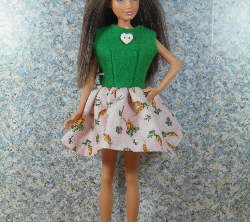 In this photo, Mattels Skipper wears a super easy to sew Easter dress. The bodice is made of easy to sew felt with a tiny heart shaped button on it while the short flared gathered skirt of the dress is made of pink and green Easter print fabric. Her little orange shoes bring out the orange carrots on the bunny rabbit print cotton skirt.