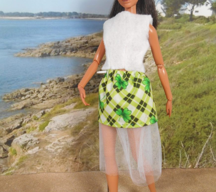 Here we see a Mattel Barbie doll at a beach. She wears a white felt sleeveless shirt with a green plaid minis skirt. Beneath the miniskirt, the petticoat is made of white tulle and it extends about an inch and a half below the hem of the miniskirt.