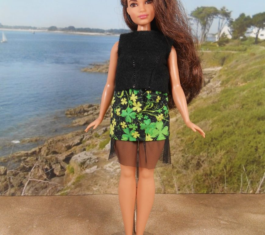 Here we see a lovely Curvy Barbie (from Mattel) modeling a black felt sleeveless shirt and a shamrock-decorated cotton mini skirt with a petticoat of black tulle. She stands on the sand at a beach.