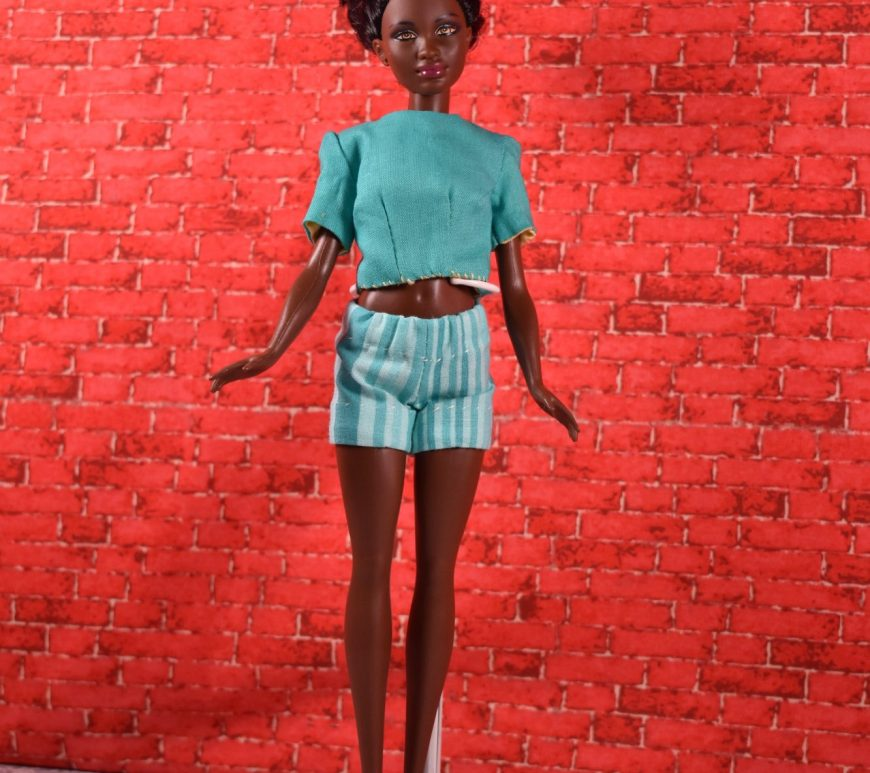 Standing before a red brick wall stands an African American or African Mattel Petite Barbie doll. She wears close fitting striped teal colored shorts with a matching teal blouse. Her little dark chocolate tummy is slightly exposed between the elastic waist of the shorts and the slightly cropped blouse with short sleeves.