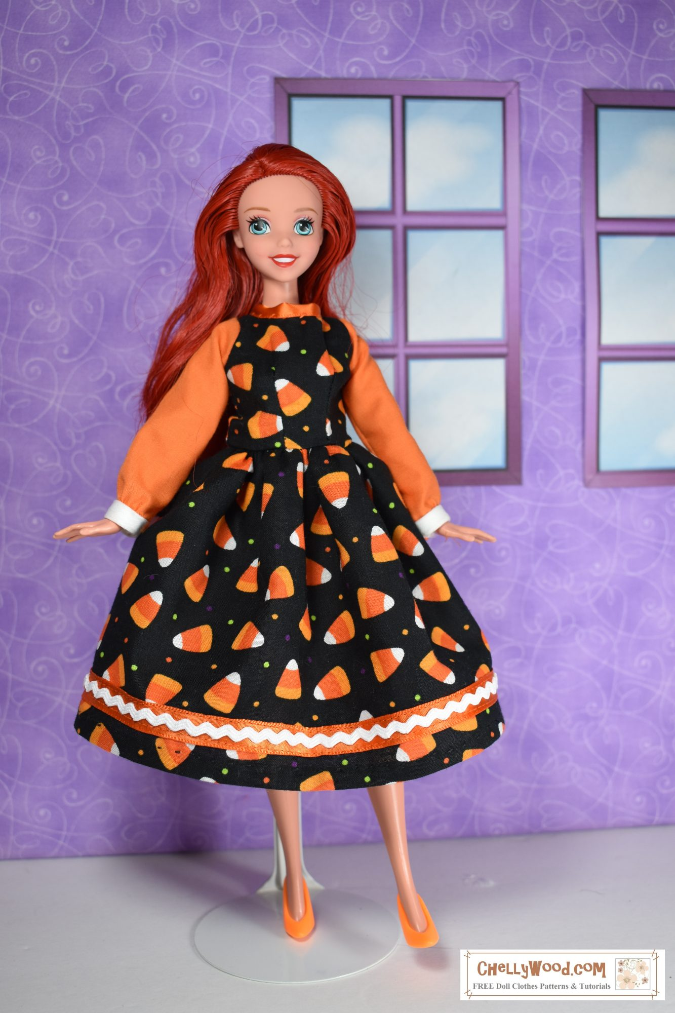 The image shows an Ariel doll wearing a long-sleeved dress with cuffs and rickrack trim. The cotton fabric of the dress is decorated with candy corn print.