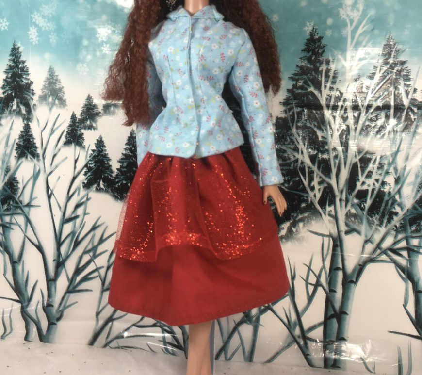 In a snowy landscape, a Tonner doll with long wavy auburn hair models a red glittery holiday skirt and a button up long sleeved shirt. The skirt is red. The shirt is pale blue cotton dotted with tiny red floral print. The shirt has a collar.