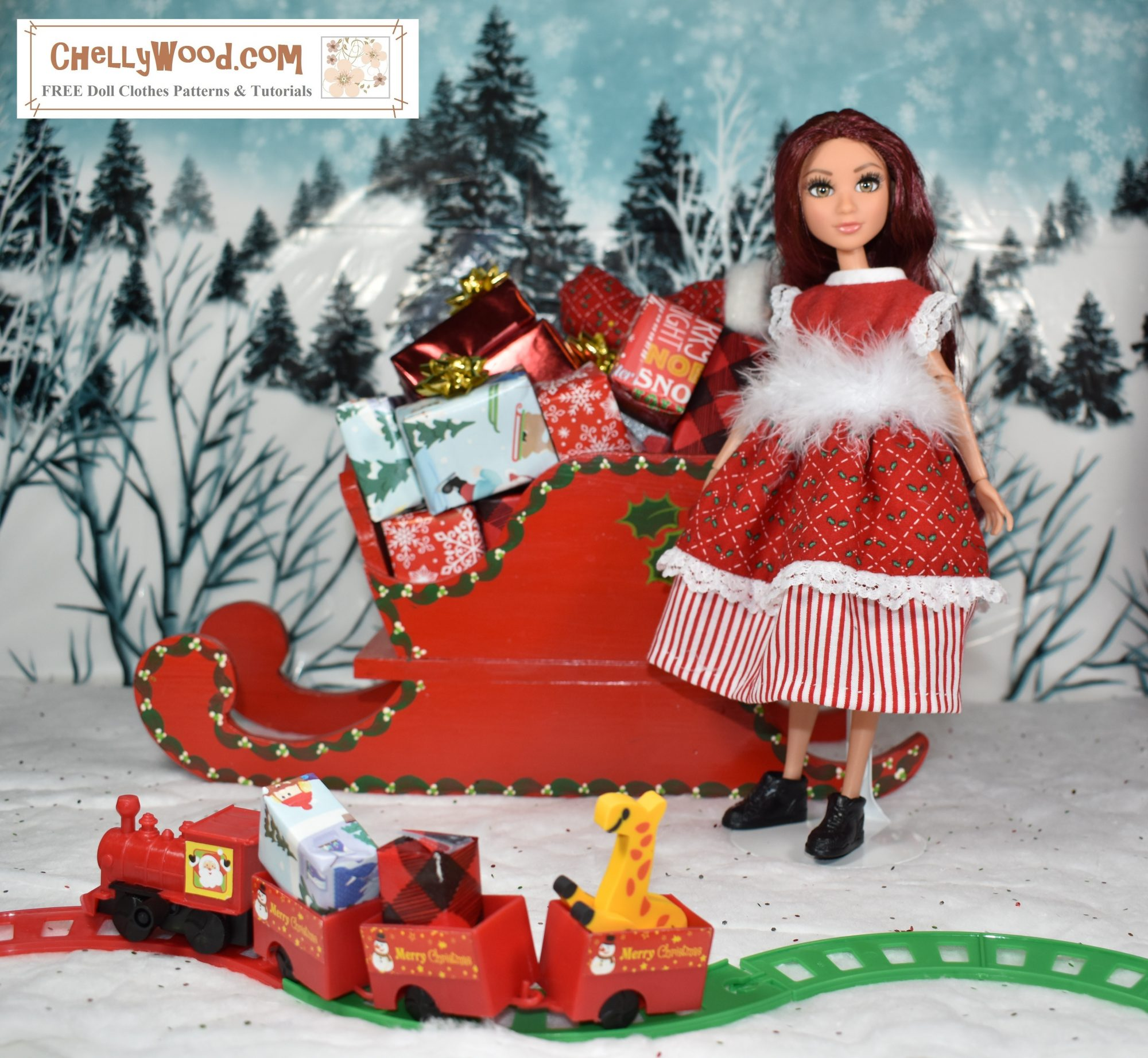 Here we see a Project MC Squared Camryn Coyle doll modeling a red Christmas dress in a North Pole diorama. Behind her is a Santa's sleigh filled with presents, and beyond that, the snowy hills are dotted with pine trees. In the foreground, there's a tiny toy train running along a little train track, delivering miniature presents. The doll's dress is made of red cotton fabric with a red and white striped cotton petticoat. Her belt is made of white fur, and her sleeves are lacy. She wears little black elf boots.