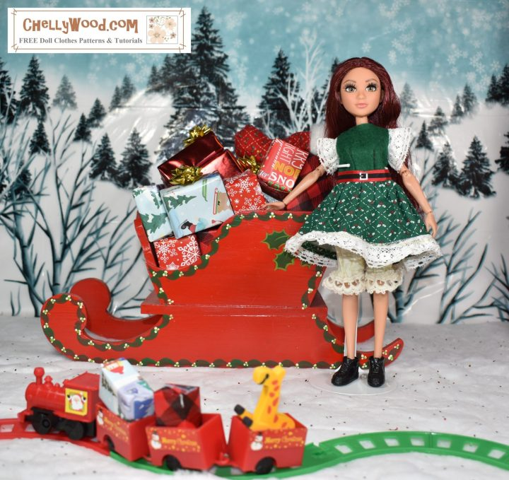 This image shows Project MC Squared Camryn Coyle doll dressed in a green Christmas dress. The dress has lace trim at the sleeves and at the bottom of the skirt, as well as a Santa-style red ribbon belt with tiny yellow buckle. Under her dress, the doll wears lacy bloomers and a pair of elf boots. She's standing in a North Pole scene, complete with snowy hills, a sleigh full of toys, and a tiny toy train running on tracks nearby.