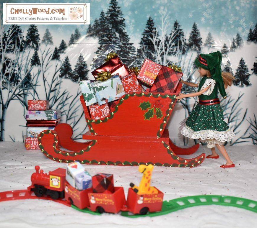 Here we see a Mattel Stacie doll giving Santa's sleigh a push in the snow. Behind her is a snowy hillside dotted with trees. Santa's sleigh is loaded with gifts, as is the tiny train in the foreground. Stacie wears an elf's hat with a Green Christmas-themed dress. the dress's bodice is made of green felt. The dress's skirt is made of holiday print green cotton fabric, and it's trimmed in eyelet. Her belt looks like Santa's with red ribbon and buckles. Her sleeves are made of lace.