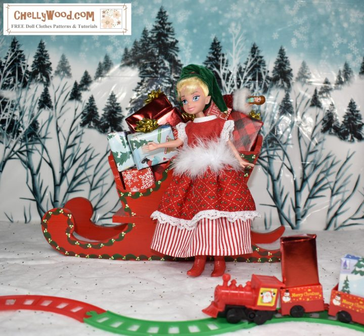 Please visit ChellyWood.com for free, printable sewing patterns for dolls of many shapes and sizes. Image shows a Tinkerbell doll (from the Disney Princess line of dolls) dressed in a hand-made Christmas dress and elf hat. She stands before a tiny train filled with gifts and toys. She leans against Santa's sleigh, which is filled with little wrapped gifts. Behind her is a snow-covered hill with many wintery pine trees.