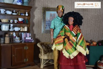 """In a dining room, with a large china hutch behind them, we see a male and female African or African American doll couple standing in peaceful ambiance. They wear clothing in bright African prints and pretty solids. The male doll (a Texas A and M Ken doll) wears a green geometric print shirt with a yellow and green and black African print hat. The deep yellow of his trousers match the yellow in his hat. The female doll, which is a """"Photographer"""" doll made by Lammily LLC, wears a red shiny skirt with a red felt shirt, and an African print yellow and green and red and black poncho over the top. Her poncho is trimmed in yellow fringe. Behind them on the wall is a famous painting of the Notre-Dame de Paris cathedral. Their dining room furniture is made of tan wicker."""