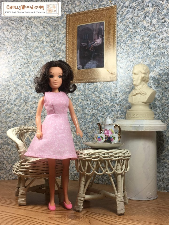 In this photo, we see a Hasbro vintage World of Love doll standing in an elegant diorama which includes wicker furniture, a tiny tea set, a bust of a famous musical composer, and a famous painting from Romeo and Juliet framed in gold. The doll wears a pretty pink floral A-line dress with darts and no sleeves.