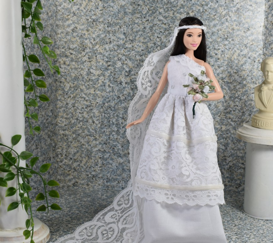 Visit ChellyWood.com for free printable sewing patterns for doll clothes to fit dolls of many shapes and sizes. Image shows Tall Barbie from Mattel's Fashionista line wearing a wedding dress that has been hand-made along with a DIY wedding bridal veil. She holds a bouquet of handmade silk ribbon flowers in miniature. The diorama she stands in includes the bust of a classical musician on a pedestal and a white pillar decorated with a leafy vine of tiny leaves trailing down to where Barbie stands with her elegant lace veil trailing behind her as a wedding train. The barbie doll smiles gracefully as if she's truly joyful about exchanging vows with Ken. To download the free patterns and view the tutorial videos for making a full ensemble of wedding clothing for barbie, Ken, and other dolls, visit ChellyWood.com and its affiliate youtube channel.