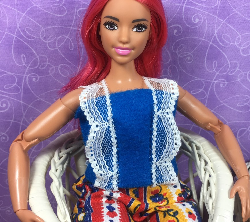 "Please visit ChellyWood.com for FREE printable sewing patterns and tutorials for dolls of many shapes and sizes. The image shows Curvy Made-to-Move Barbie wearing a Barbie-sized felt summer top with lace straps. The overlay says, ""ChellyWood.com: FREE printable sewing patterns and tutorials for dolls of many shapes and sizes."" This is a preview image of the doll clothes patterns and tutorials that will be posted on ChellyWood.com this week. We will learn how to sew this easy-to-make DIY summer shirt (summer top) which fits a number of 11-inch, 11 and a half inch, and 12 inch fashion dolls including Barbie, made-to-move Barbie, Tammy dolls, Curvy Barbie dolls, and MTM Curvy Barbie dolls. The Barbie doll clothes summer shirt pattern is going to be free and printable like all of my other dolls' clothes patterns."