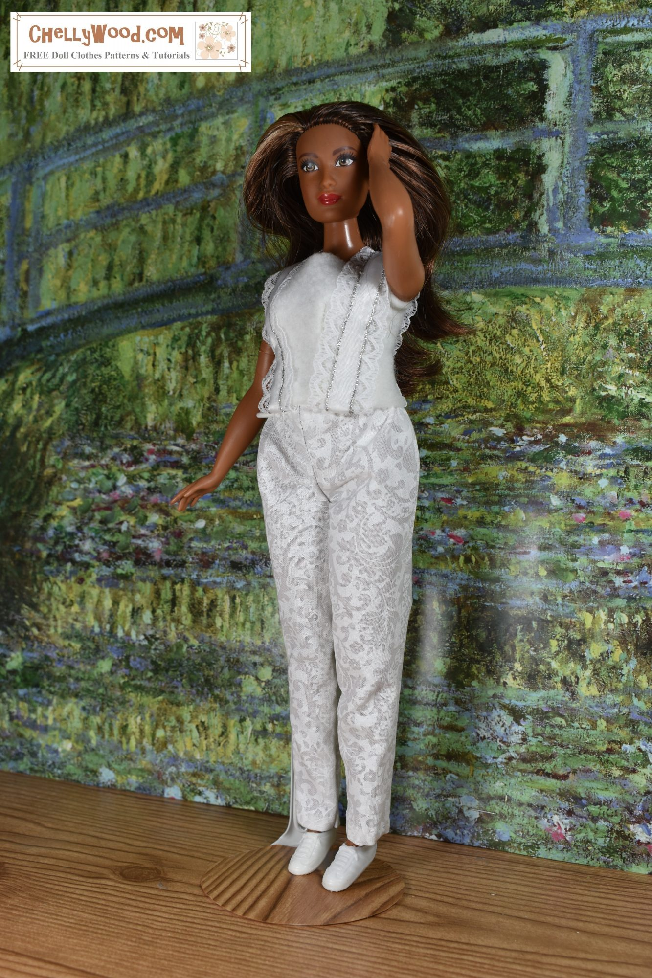 In this image, a Curvy Barbie runs her fingers through her hair while standing in front of a painting of Monet's Green Bridge. She wears a pair of white elastic-waist pants that are cropped at the ankles. She also wears a white felt slimming tank top with lace straps that embellish the front (and back) of the white felt shirt.