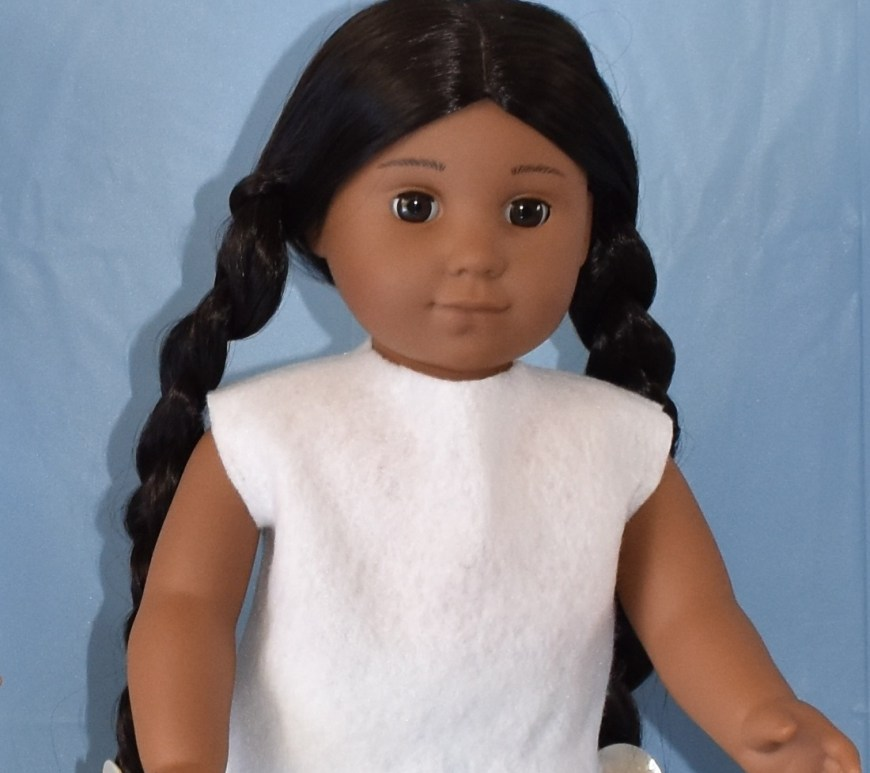 "Image shows Kaya an American Girl 18-inch doll wearing an easy-to-sew felt shirt made using a free pattern which is downloadable at ChellyWood.com. The doll stands in front of a blue background with her arms outstretched in a welcoming manner. Her expression is content. The overlay says: ""ChellyWood.com"" and offers the explanation that this website offers ""free doll clothes patterns and tutorials."" The page where this image is found says ""later this week I'll be posting the free printable sewing pattern and tutorial to help you make this easy-to-sew felt shirt that will fit most 18-inch dolls like American Girl dolls and Madame Alexander dolls."""