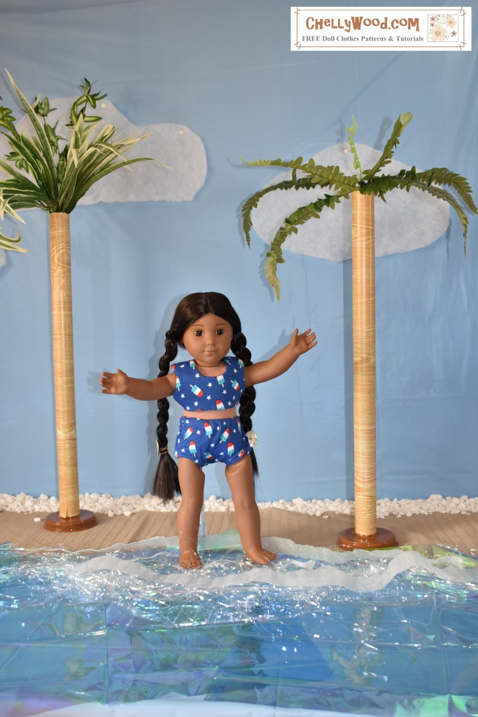 An American Girl 18 inch Kaya doll stands on a beach, dipping her little toes in the waves, with arms outstretched toward the blue sky. On her left and right sides are palm trees. She wears a handmade bikini made of blue jersey fabric decorated with tiny popsicles in red and white.
