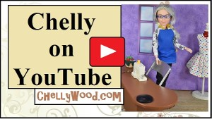 "The image shows the Chelly Wood doll at her sewing table with a dress form in the background. The doll has grey hair and wears a blue apron. On her tiny sewing table lie a pair of miniature sewing scissors and a miniature pincushion. The overlay says, ""Chelly on YouTube"" and below it is the website's URL: ChellyWood.com (where you can find lots of free printable sewing patterns for making doll clothes for various sized dolls). The whole image lies behind a superimposed ""play"" icon in the YouTube iconic red button with white triangle image."