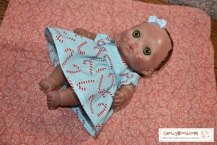 Please visit ChellyWood.com for FREE printable sewing patterns to fit dolls of many shapes and sizes. The image shows a Bibi doll from JC Toys modeling a baby doll dress with puff sleeves. She lies on a handmade blanket. This adorable baby doll dress pattern is free to print at ChellyWood.com.