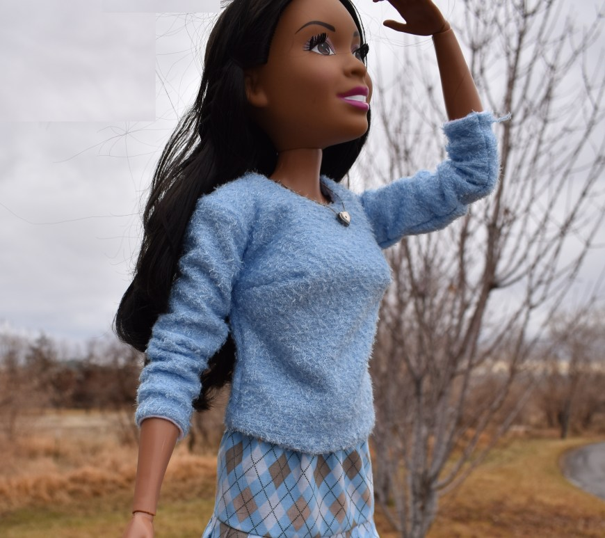 The image shows a 28 inch best Fashion Friend Barbie doll by Mattel. She's in a winter outdoor setting with a bare tree behind her and yellow grass. A road winds around the corner behind her as well. She looks out at the wintery landscape with one hand over her eyes to shade them. This 28 inch Barbie doll models a handmade shirt made of sweater material. She also has a heart-shaped necklace on and a handmade skirt. The skirt has knife pleats and is made of tan and blue argyle fabric. This doll's clothes were made using the free doll clothes patterns available at ChellyWood.com and the URL is on the watermark for the image of this doll. ChellyWood.com offers free printable sewing patterns for dolls of many shapes and sizes, including but not limited to free sewing patterns for 28 inch Barbies.