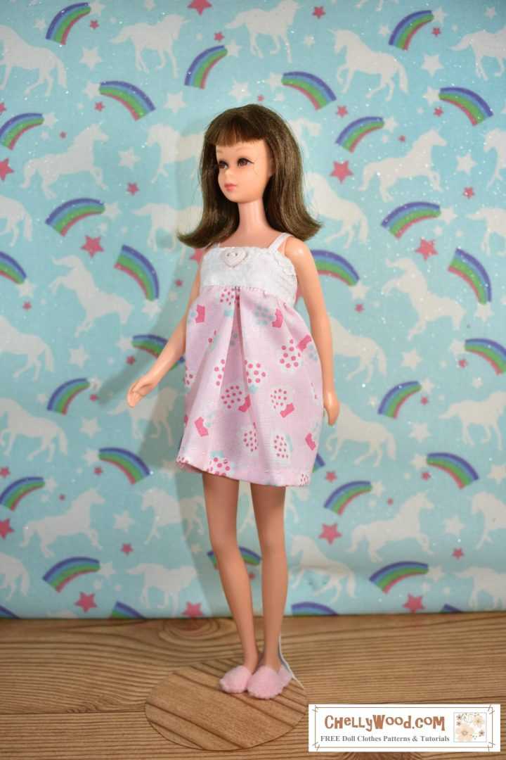 Here we see a vintage Francie doll walking in pajamas and handmade slippers. She's walking on a hardwood floor with unicorn-and-rainbow wallpaper behind her. The cotton fabric of her short nightgown is decorated with tiny cupcakes. The bodice of her nightgown is white lace, and the nightgown also has little ribbon straps.