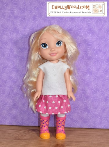 The image shows a 13-inch Elsa Disney Princess hard plastic doll wearing a hand-made pink skirt with white polka dots. The skirt has an elastic waist. She also wears an easy-to-sew felt shirt with barely a cap sleeve. Tiny white buttons run down the front of the felt shirt. To make this outfit for your 13 inch Disney Animators toddler doll, please click on the link in the caption, and it will take you to all the free printable PDF sewing patterns and tutorial videos you'll need to sew this outfit.