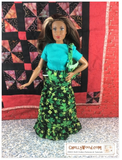 The image shows a Mattel Curvy Barbie doll wearing a handmade maxi skirt that is made of black glitter fabric decorated with gold and green shamrocks. The skirt itself is tiered with a ruffle at the bottom. The doll also carries a matching purse, made of the same fabric. The free printable patterns for making these come from ChellyWood.com, where you can also find free tutorial videos showing you how to make teach item of clothing.