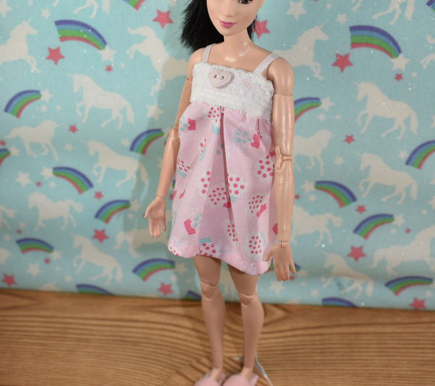 A made-to-move Barbie models a short pajama nightgown made of cotton and lace with straps. She also wears handmade felt slippers. She stands before a bedroom wall that's decorated with unicorns and rainbows. Her expression is sleepy-eyed.