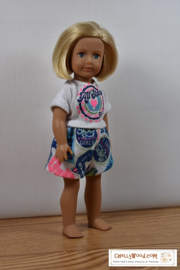 "The image shows the 6-inch American Girl doll wearing a pair of handmade shorts and a matching T-shirt. The watermark on this image says ""ChellyWood.com"" which is a website offering free printable sewing patterns for making doll clothes like the outfit shown here."