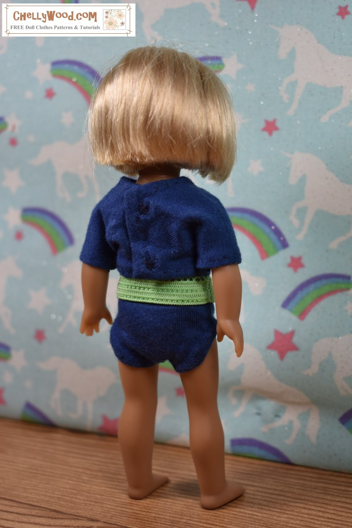 """The image shows a 6-inch American Girl doll modeling a pair of handmade briefs (underpants / knickers) with a handmade T-shirt (tee shirt). The watermark says """"ChellyWood.com"""" which is the URL of the website where you can download free printable sewing patterns for doll clothes, including this pair of underpants and this shirt pattern for 6 inch dolls like American Girl. In this image, the doll has her back to the camera, so you can see that the back closure uses snaps."""