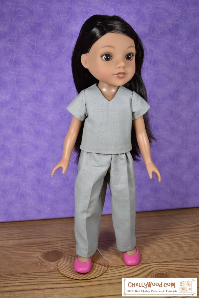 """Here we see a Hearts for Hearts Consuelo doll wearing what appears to be """"scrubs"""" or at least a short-sleeved V-neck shirt with matching grey cotton trousers."""
