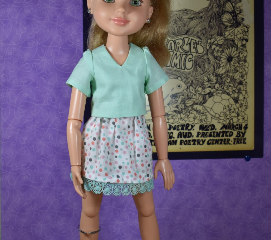 Standing in an art gallery with a graffiti-like painting behind her, a BFC Ink doll (best friends club ink) models a V-neck blouse with an elastic-waist random dot cotton skirt that's trimmed in crocheted lace.