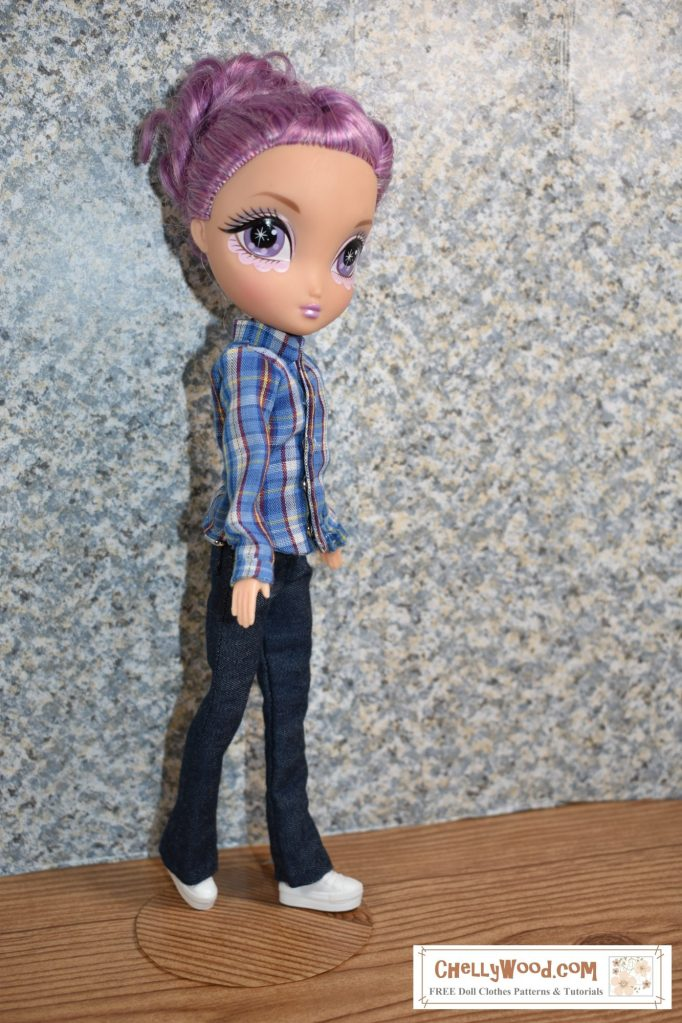 A Spin Master La Dee Da doll stands before a concrete wall. She appears to be walking in boot cut jeans and a blue plaid long sleeved shirt. The shirt has a tiny collar and cuffs. The dolls miniature white sneakers have extra thick soles. She gives the camera a sidelong glance.
