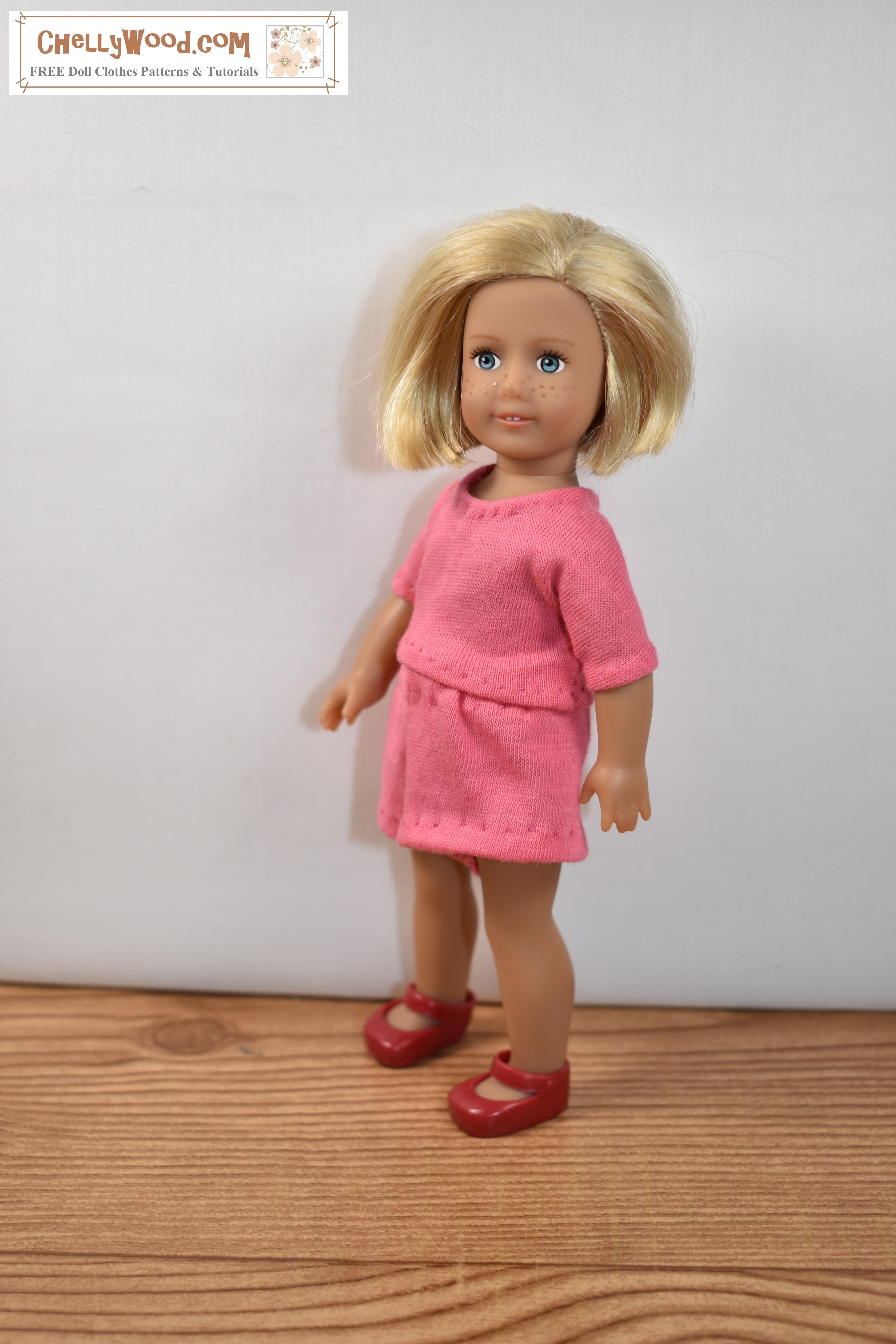 The image shows a 6-inch American Girl doll wearing handmade doll clothes that include a pair of elastic-waist jersey-fabric shorts and a matching T-shirt in salmon-colored jersey fabric. Click here for the free printable PDF sewing patterns and free tutorials to make this outfit.