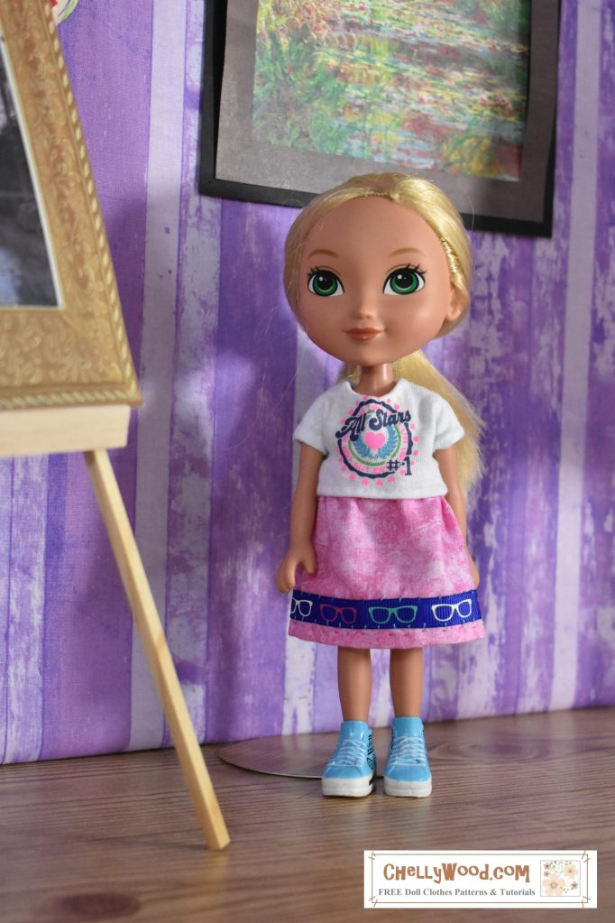 """Dora's friend Alana models a handmade graphic tee and a pink elastic waist skirt with a ribbon trim. The shirt is white with a graphic that says """"all stars"""" and the skirt is pink with a blue ribbon as trim. The blue ribbon is decorated with tiny sunglasses in pink, turquoise blue, and white, pulling the whole color scheme of Alana's outfit together."""