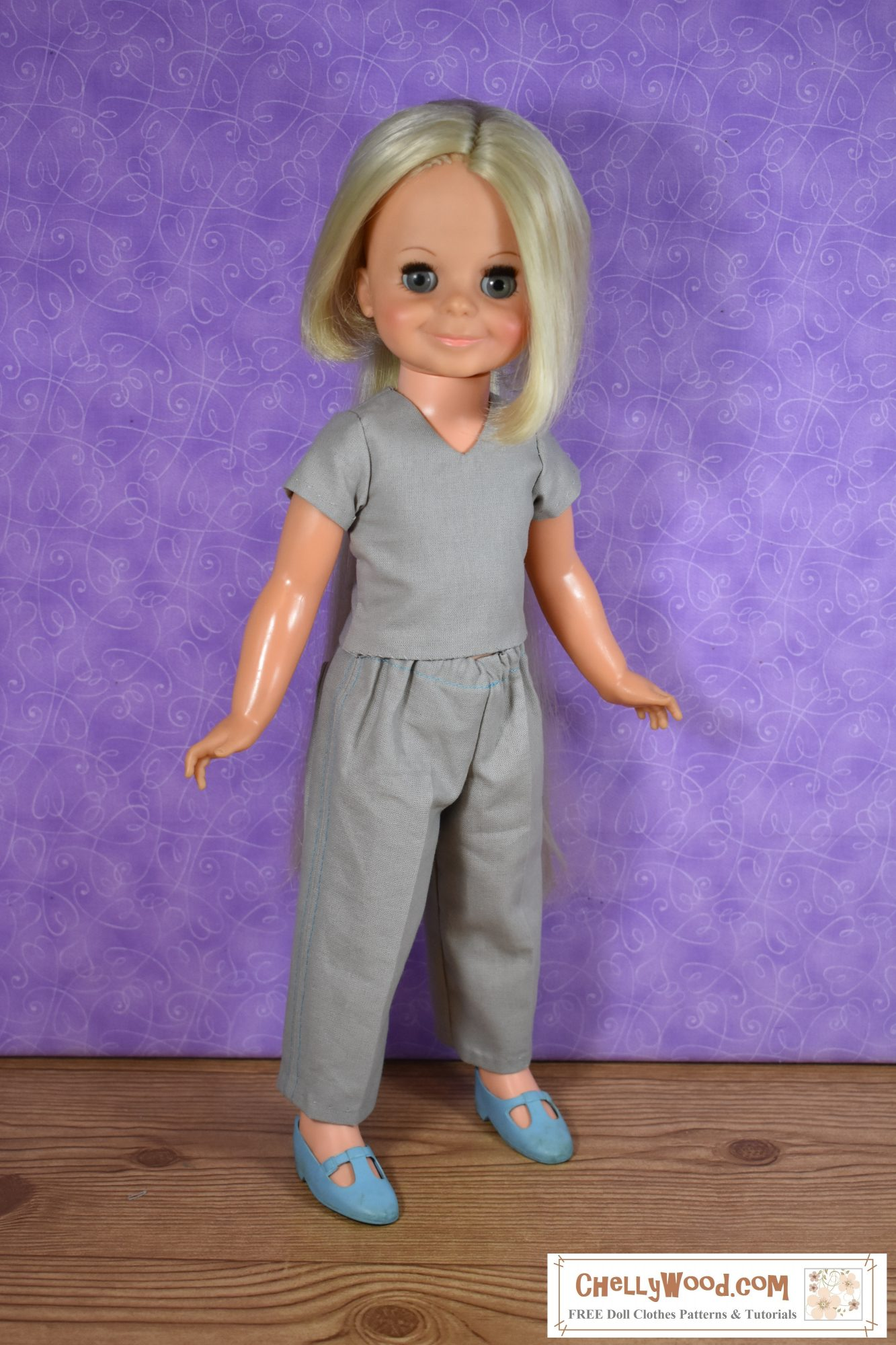 Here we see a vintage Velvet doll with her long blond hair hidden. That's because she's dressed in a nurse's scrubs for this photo: a short-sleeved V-neck grey cotton shirt and grey cotton pants with an elastic waist.