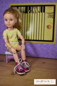 A BFC Ink doll sits on a stool in front of a poster that appears to be part of an art gallery. The poster looks sort of like piano keys that morph into a name: Kinnell. the doll sports a yellow shorts and shirt set. The shirt or blouse has a square neck and is trimmed in lace. The shorts, which are sort of hidden by her arm as she rests it on her knee, have an elastic waist. She wears shiny pink high-top sneakers.
