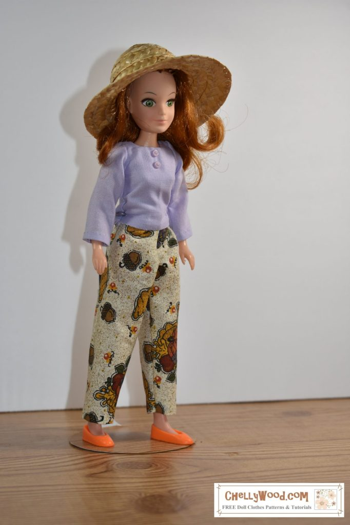 """The image shows """"Flower"""" (a doll from the World of Love collection) wearing handmade doll clothes including a pair of ankle pants and a long-sleeve shirt. The free printable sewing patterns for these doll clothes are found at chellywood.com"""