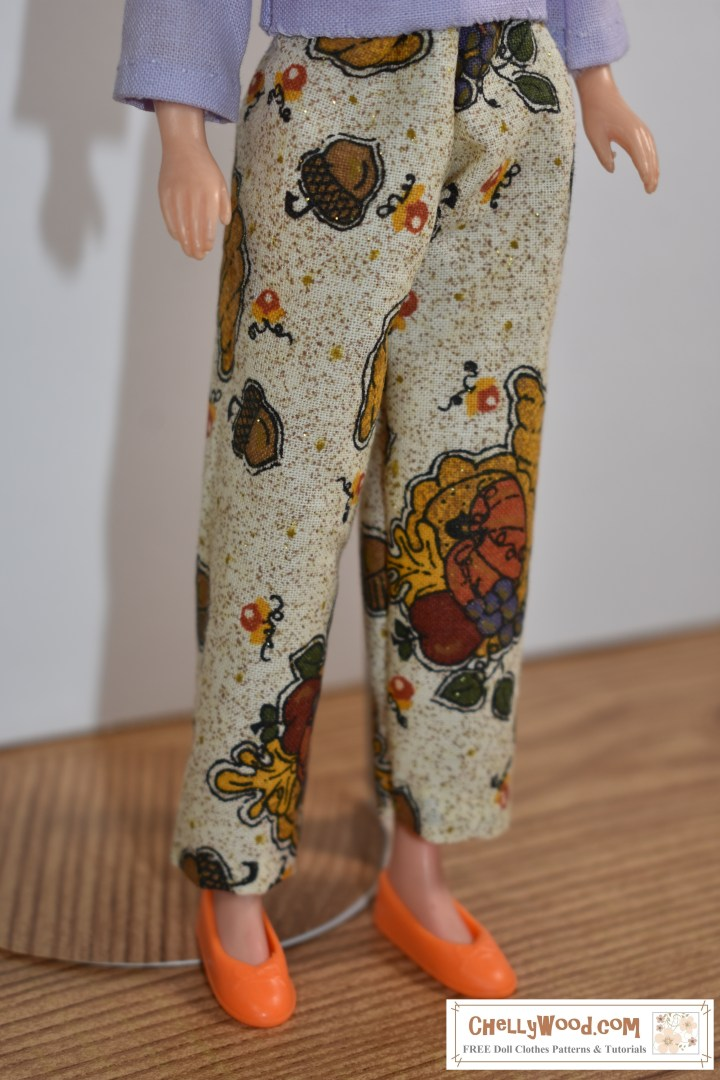 """This week we'll be sewing these ankle pants for 9 inch fashion dolls like the World of Love """"Flower"""" doll shown in this image wearing a pair of tiny ankle pants with a harvest-themed pattern (decorated with acorns, leaves, autumnal flowers, and a few cornucopias scattered across the fabric). To download the free printable sewing patterns for making the ankle pants and the accompanying doll clothes, please go to ChellyWood.com"""