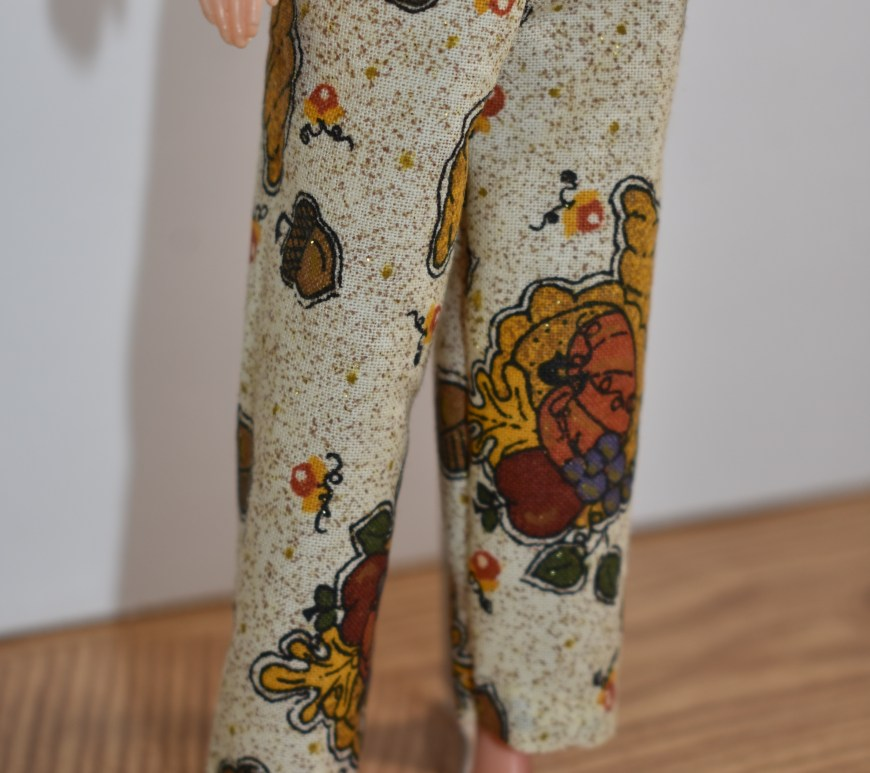 "This week we'll be sewing these ankle pants for 9 inch fashion dolls like the World of Love ""Flower"" doll shown in this image wearing a pair of tiny ankle pants with a harvest-themed pattern (decorated with acorns, leaves, autumnal flowers, and a few cornucopias scattered across the fabric). To download the free printable sewing patterns for making the ankle pants and the accompanying doll clothes, please go to ChellyWood.com"