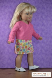"This photo shows a cute little blond-haired 18 inch doll who appears to be walking, taking steps in her Sunday best. She wears a pink long-sleeve cotton shirt with a slight V-neck and teeny-tiny white polka dots and a yellow skirt that has little pastel-colored flowers that seem to also be spotted with polka dots. At the bottom of the image, near her high-stepping MaryJane shoes, there's a watermark: ChellyWood.com . On this website, you'll find hundreds of free printable PDF sewing patterns for making doll clothes to fit dolls of many shapes and all different sizes. Each pattern has been watermarked with the URL ChellyWood.com and the ""Creative Commons Attribution"" mark, which means that by downloading these free doll clothes patterns, you agree to share images of the patterns with your family, friends, and followers, letting people know where you got the patterns."