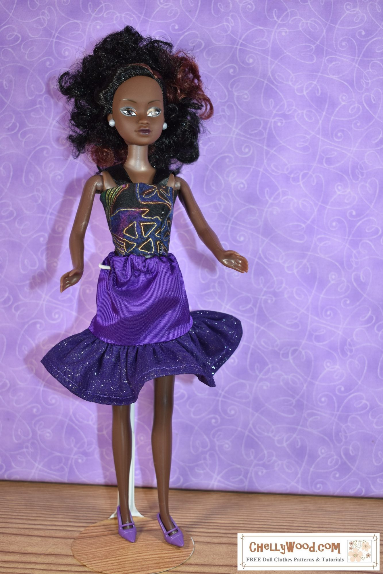 Visit ChellyWood.com for free printable sewing patterns and tutorials for sewing doll clothes to fit dolls of many shapes and sizes. The image shows a Queens of Africa 11 inch fashion doll wearing a handmade pair skirt with a ruffle and a strappy summer top in purple, black, and gold colors. The Queens of Africa dolls can be purchased from the Slice by Cake company at https://queensofafricadolls.com/