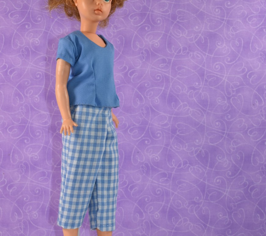 The image shows Ideal Toy Corp's 1960's Tammy doll (the ideal teen) wearing handmade blue gingham pedal pusher pants and a handmade matching solid blue short sleeved cotton shirt with a scoop neck. The overlay watermark offers the URL of the website where you can find all the free printable sewing patterns for making these doll clothes: ChellyWood.com