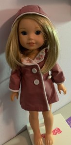 A blond Wellie Wisher doll is shown wearing a handmade lined raincoat in pink colors. The pattern used to make this raincoat can be found and downloaded for free at ChellyWood.com but the outfit was made by blog follower Dorothy (Dottie) L.