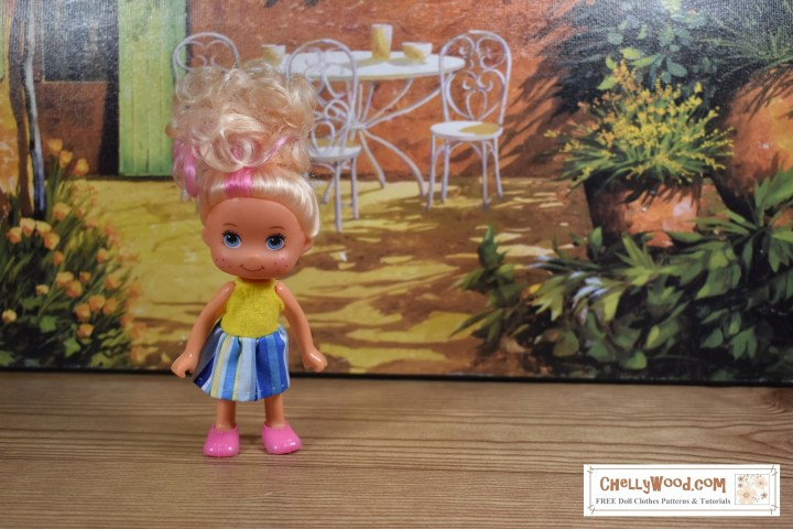 Please visit ChellyWood.com for free printable sewing patterns for making doll clothes to fit dolls of many shapes and sizes. This image shows a 4-inch doll (a Greenbrier doll) wearing a handmade dress. The bodice of the dress is made of yellow felt and the skirt is made of blue and yellow striped cotton. There are ribbon straps around the doll's shoulder holding the dress up.The doll stands on a wooden walkway beside a tiny cafe. This doll's clothing represents a miniature sundress that you could sew using Chelly Wood's free printable PDF sewing patterns (found at ChellyWood.com).