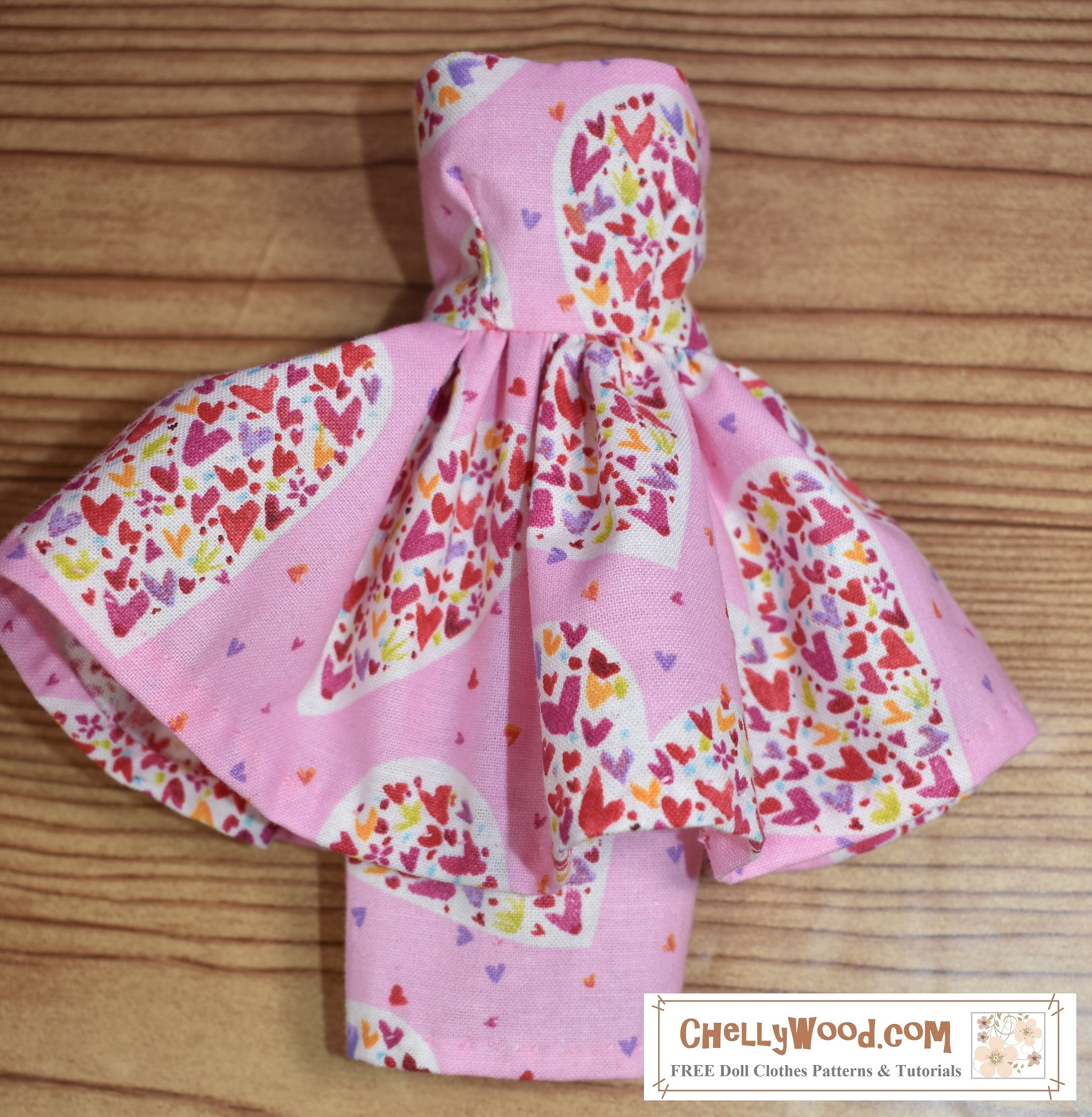 Here we see a strapless dress for fashion dolls. The dress has a pencil skirt topped with a flouncy skirt. The fabric is pink with multi-colored hearts splattered across the fabric in random patterns.