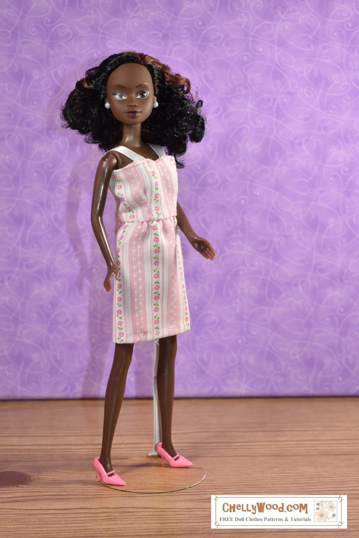 "This image shows a Queens of Africa doll wearing a pretty handmade dress made of thin pink material decorated with polka dots and flowers on pink and white striped fabric. The dress has a short, straight skirt and a summery bodice with straps made of ribbon. The watermark says, ""ChellyWood.com: Free doll clothes patterns and tutorials."" The Queens of Africa dolls have a body shape similar to a Barbie-sized doll. She stands 11 inches high and has dark chocolate complexion. Her hair is quite curly. To purchase a Queens of Africa doll, go to https://queensofafricadolls.com/"