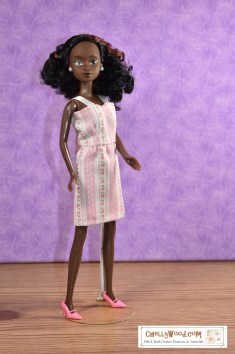 """This image shows a Queens of Africa doll wearing a pretty handmade dress made of thin pink material decorated with polka dots and flowers on pink and white striped fabric. The dress has a short, straight skirt and a summery bodice with straps made of ribbon. The watermark says, """"ChellyWood.com: Free doll clothes patterns and tutorials."""" The Queens of Africa dolls have a body shape similar to a Barbie-sized doll. She stands 11 inches high and has dark chocolate complexion. Her hair is quite curly. To purchase a Queens of Africa doll, go to https://queensofafricadolls.com/"""