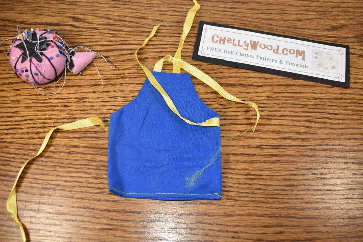 The image shows the royal blue apron worn by the Chelly Wood doll in her stop motion doll videos. The apron's ribbon has become detached.