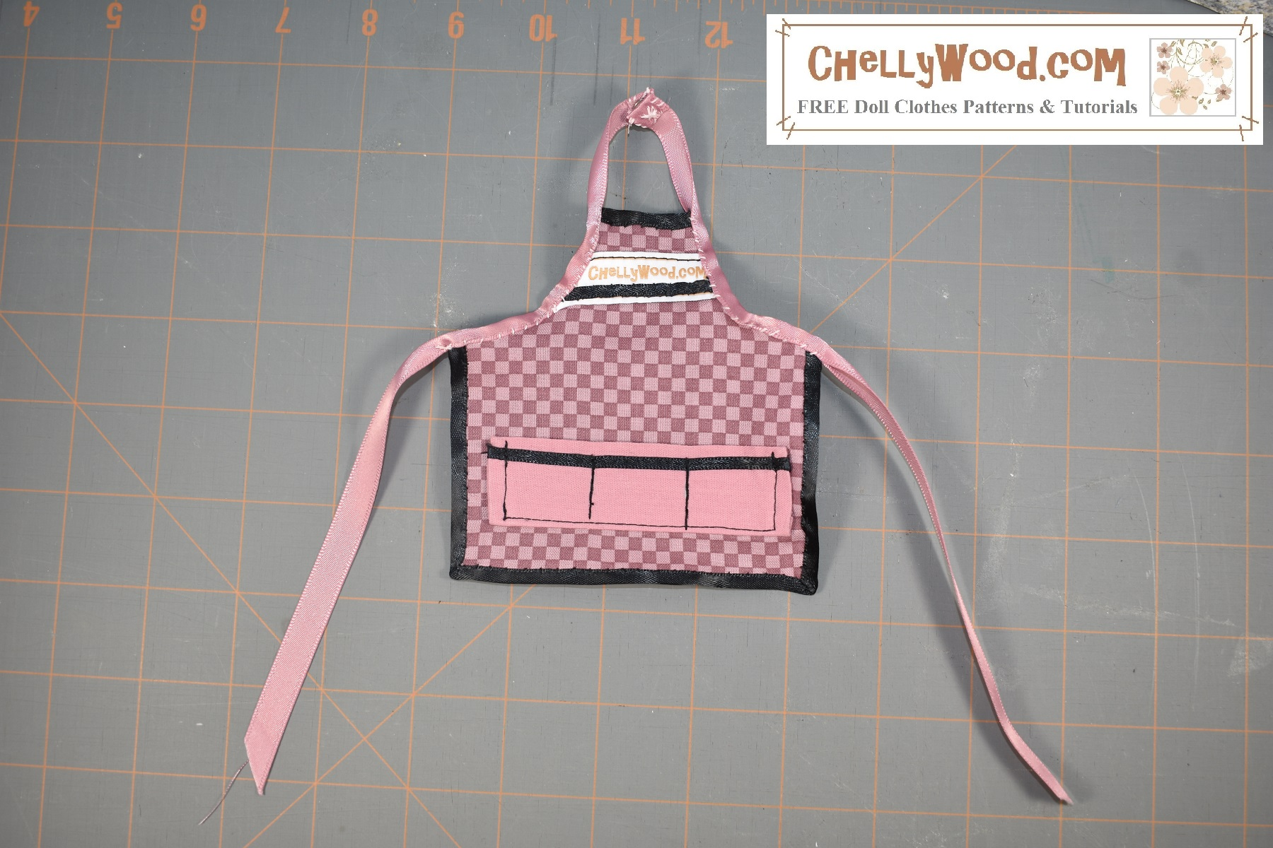This image shows a handmade apron for 11 to 12 inch fashion dolls like Barbie, Liv Dolls, Queens of Africa and Poppy Parker. The apron has three front pockets, a ribbon that ties the apron in the back, and a snap closure at the neck of the apron. The fabric of the apron is a pink checkerboard while the pockets are a solid pink fabric. Visit ChellyWood.com for the free printable sewing pattern and tutorial video showing how to make this doll clothes sewing project using our free printable PDF sewing pattern.