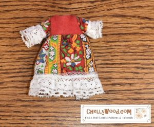"""The image shows a handmade folk-style dress that fits 4 inch, 5 inch, or 6 inch dolls (10 cm to 15 cm dolls). The dress shown uses a folksy cotton fabric for the dress's sleeves and skirt, red felt for the bodice, and the whole dress is trimmed in white lace. The watermark lets you know that if you go to ChellyWood.com, you'll find """"free doll clothes patterns and tutorials."""""""